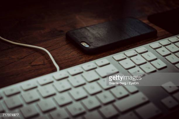 Close-Up Of Keyboard And Mobile Phone On Table