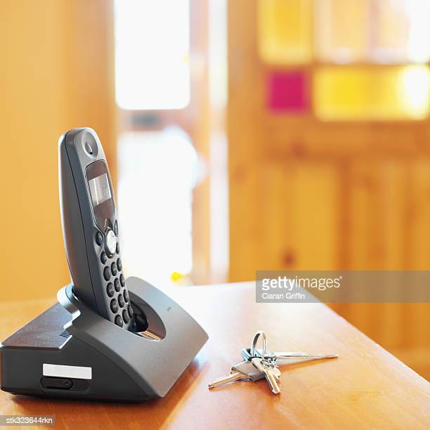 close-up of keys and a cordless phone on a table