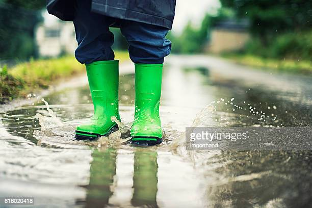 Closeup of kid's galoshes splashing in street puddle