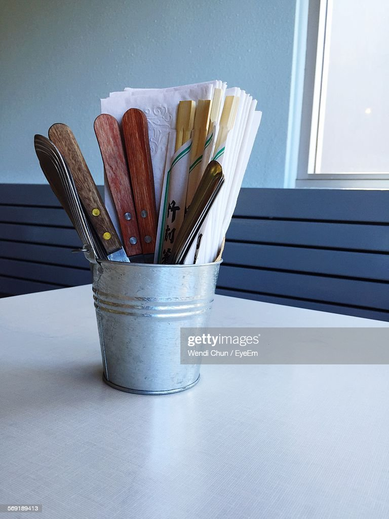 Close-up of knife and spoon in container on table by window