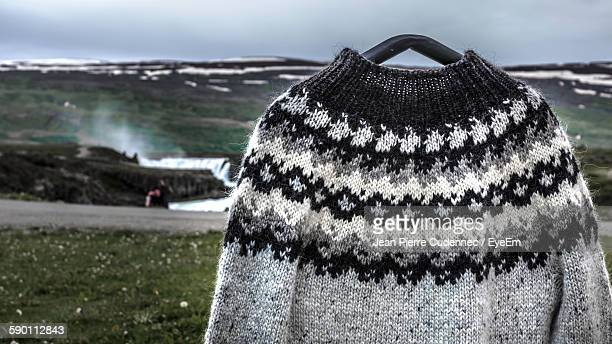 Close-Up Of Knitted Sweater Against Sky During Winter
