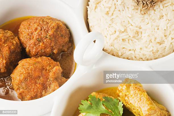 Close-up of koftas curry and boiled rice and meatballs in bowls