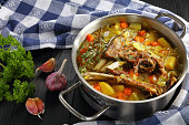 close-up of delicious Icelandic Lamb winter hot Soup with vegetables and spices or kjotsupa in a stainless steel casserole pan on wooden table with kitchen towel, traditional recipe, view from above