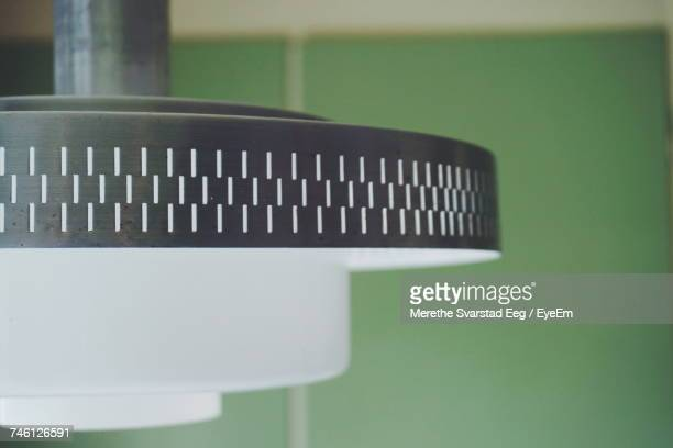 Close-Up Of Lamp Against Green Tiled Wall