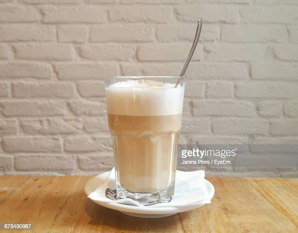 Close-Up Of Latte Macchiato On Table Against Wall
