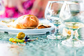 Closeup of leftovers in restaurant on table with small glass cognac whiskey rum glasses and messy dirty surface, bread