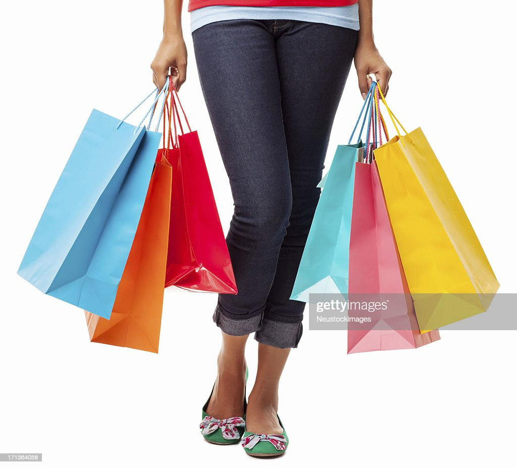 Close-up of legs of woman carrying colorful shopping bags
