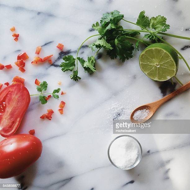 Close-up of lime, tomato and parsley on table