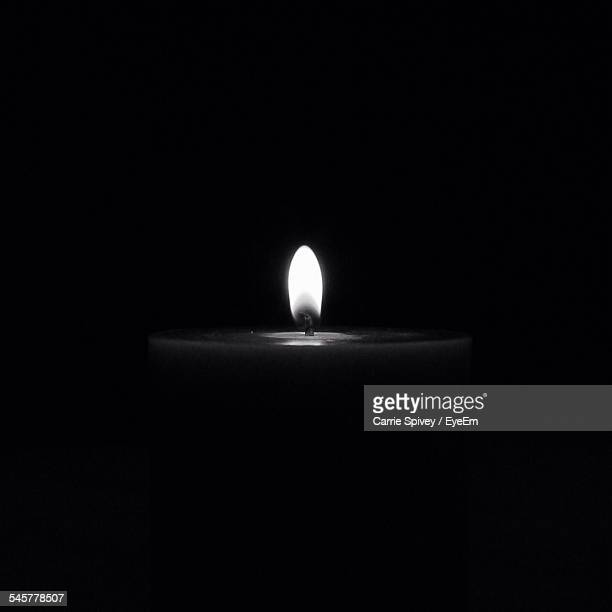 Close-Up Of Lit Candle Over Black Background