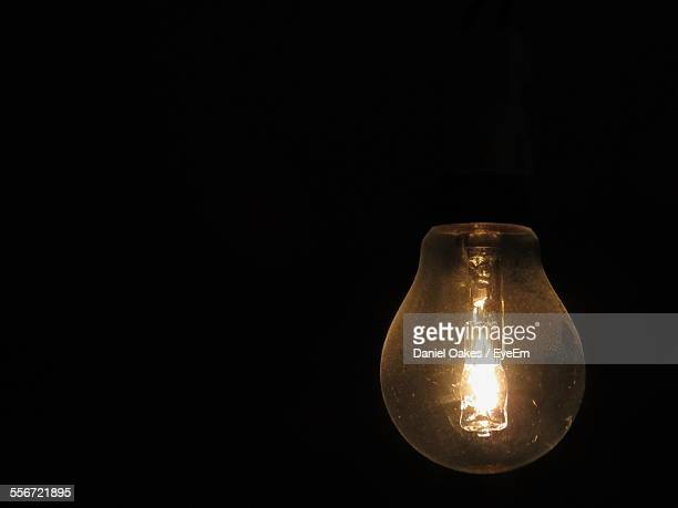 Close-Up Of Lit Light Bulb Against Black Background
