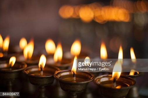 Close-Up Of Lit Oil Lamps Burning At Temple