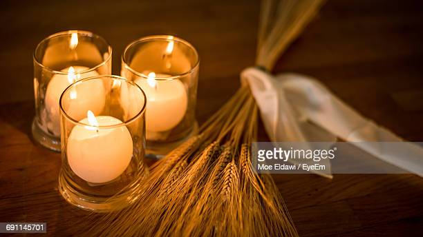 Close-Up Of Lit Tea Light Candles By Grains On Table