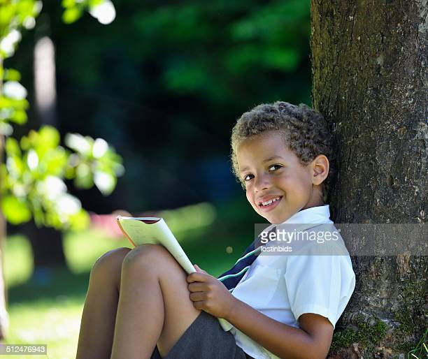 Close-up Of Little Biracial Schoolboy Reading/ Writing Outside