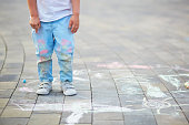 Closeup of little boy's pants stained with chalks. Children drawing on asphalt. Summer activity and creative games for small kids