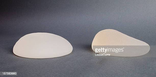 Close-up of lopsided breast implants on a table