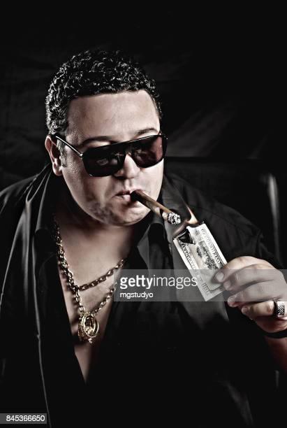 Close-up of mafia man's hand  burning  cigar with money