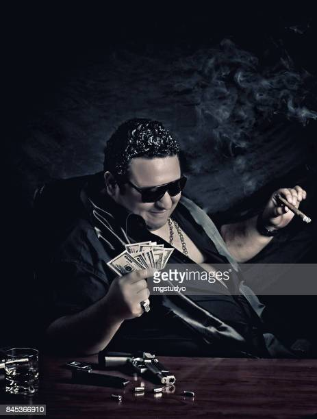 Close-up of mafia man's sitting on the chair counting money