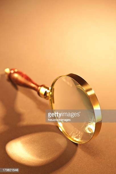 Closeup of magnifying glass over isolated background