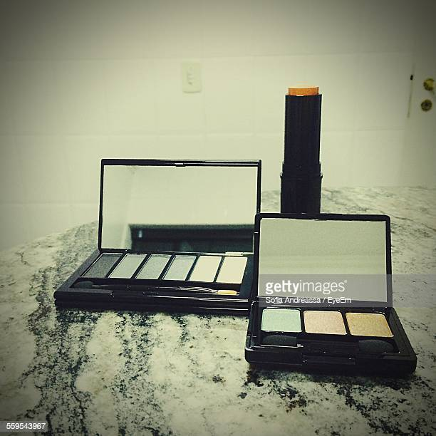 Close-Up Of Make-Up Kits With Lipstick On Table At Home