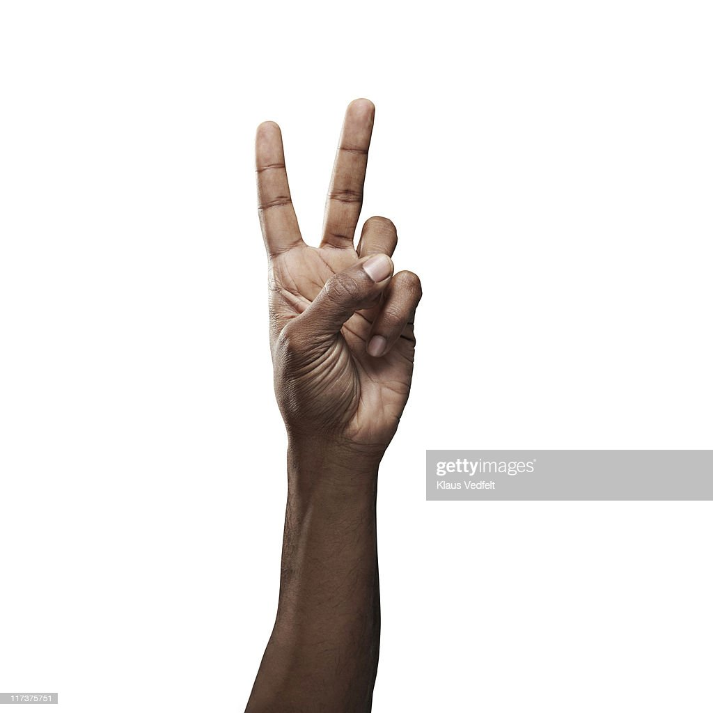 Close-up of male hand doing 'peace' sign