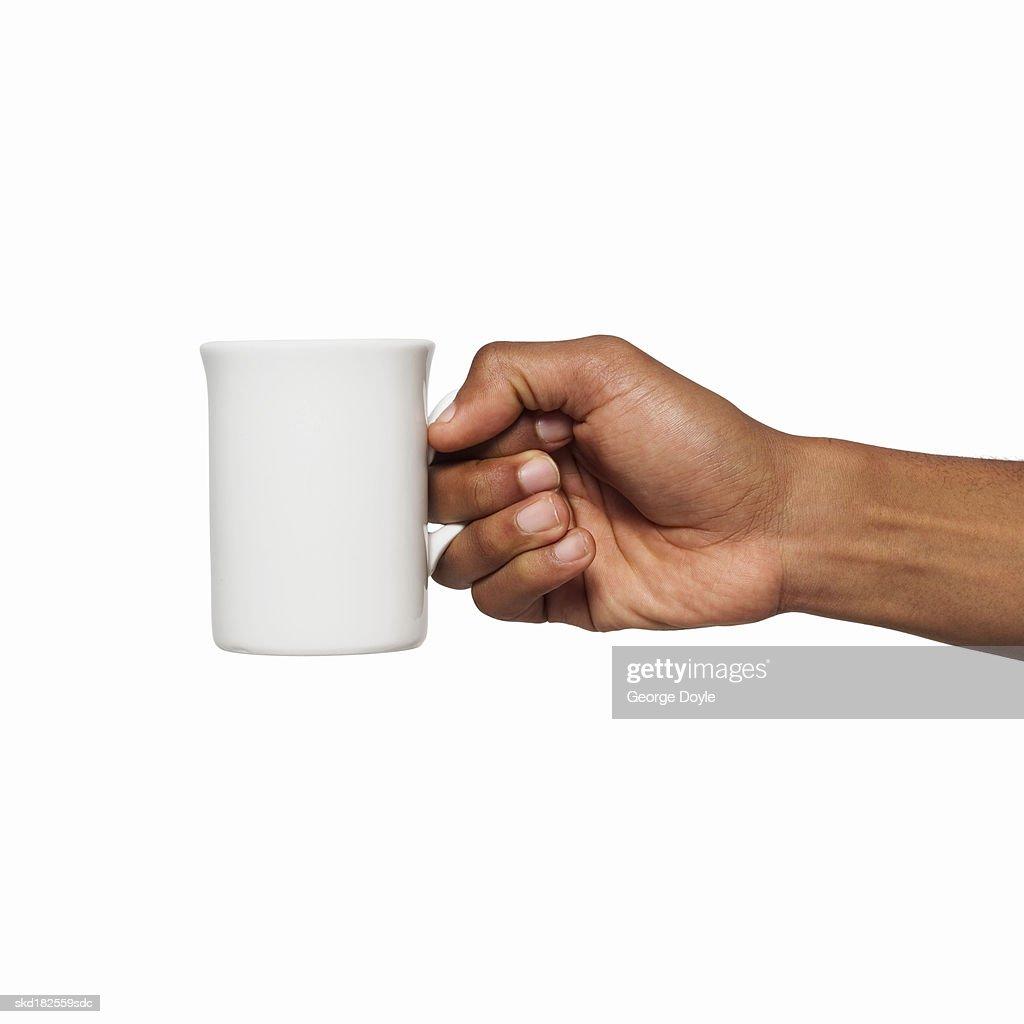 Close-up of male hand holding mug