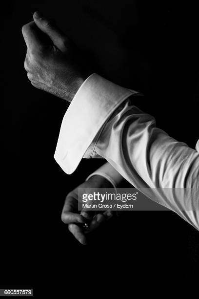 Close-Up Of Man Adjusting Cuff Link Against Black Background