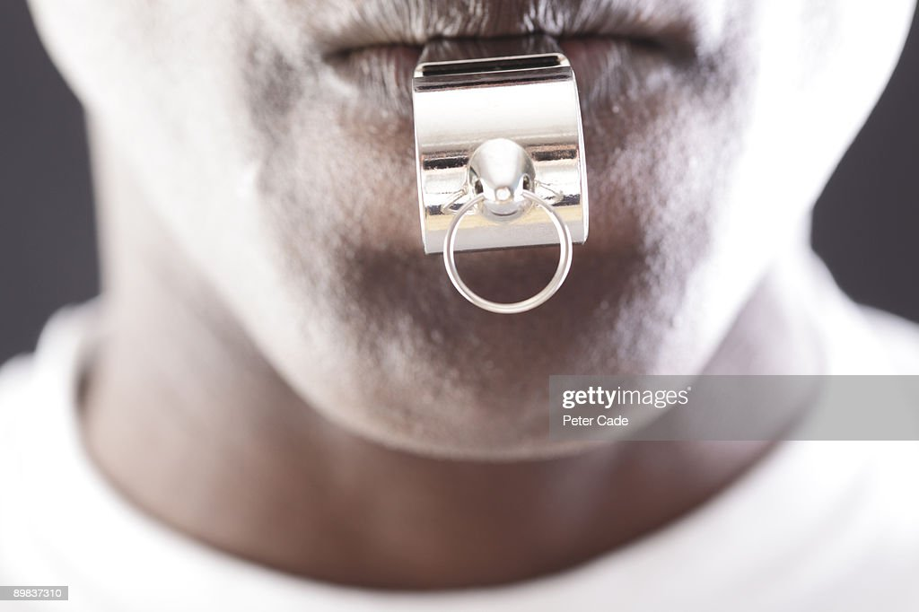 Close-up of man blowing whistle : Stock Photo