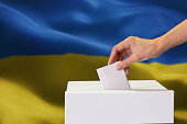 Close-up of man casting and inserting a vote and choosing and making a decision what he wants in polling box with Ukraine flag blended in background.