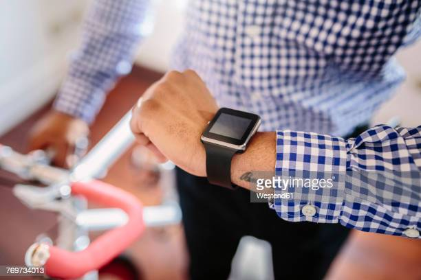 Close-up of man checking the smartwatch while holding a bike indoors
