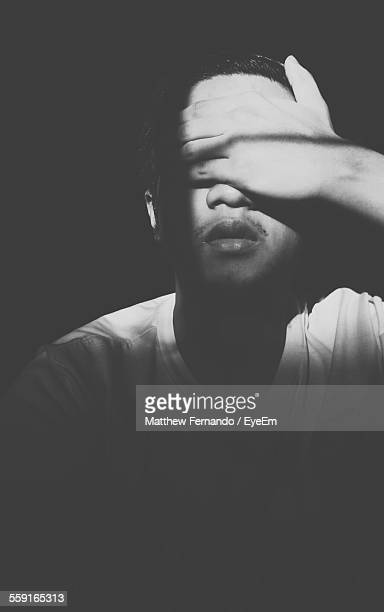 Close-Up Of Man Covering Eyes In Darkroom