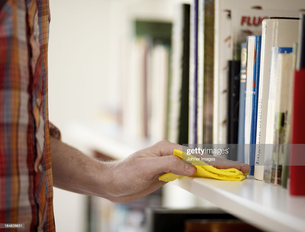 Close-up of man dusting book shelf : Stock Photo