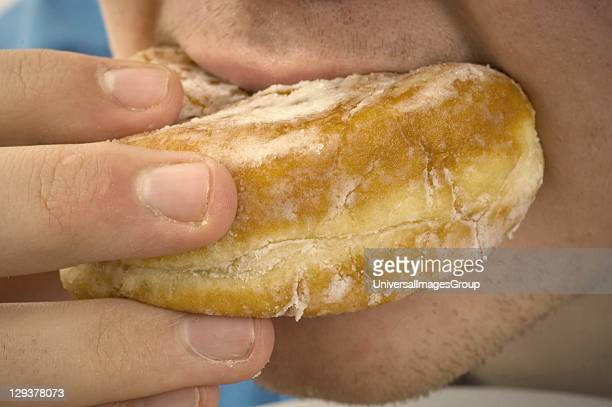 Closeup of man eating jam donut Jam donuts have been criticized by junk food activists in the global war on obesity as unhealthy with poor...