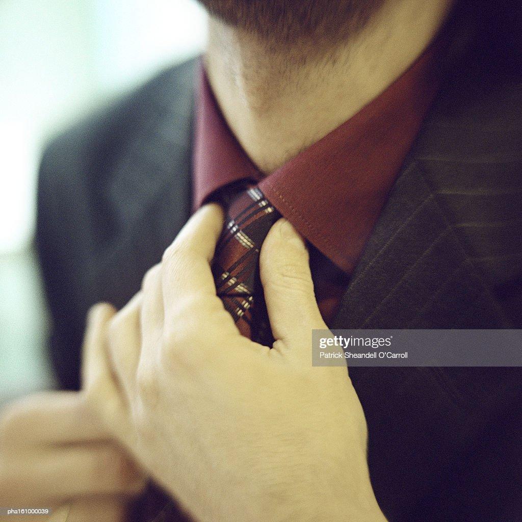 Close-up of man fixing tie. : Stock Photo
