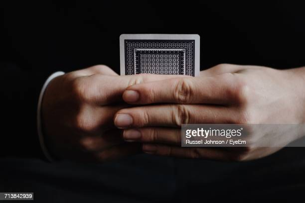 Close-Up Of Man Holding Card Over Black Background