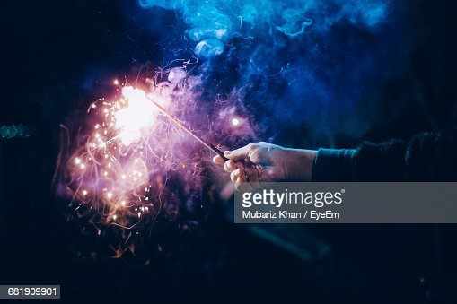 Close-Up Of Man Holding Firework At Night : Stock-Foto