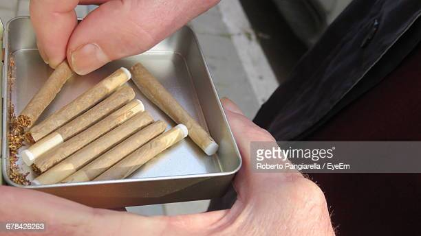 Close-Up Of Man Holding Hand Rolled Cigarettes