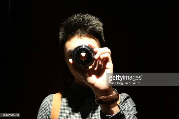 Close-Up Of Man Holding Lens In Dark