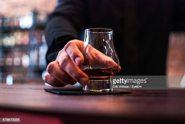 Close-Up Of Man Holding Whiskey Glass On Table In Bar