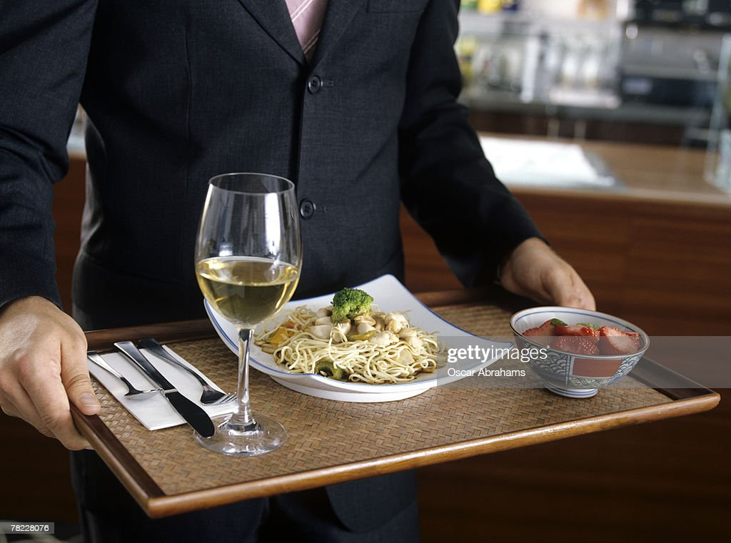 close-up of man in suit carrying a tray in a self-service restaurant