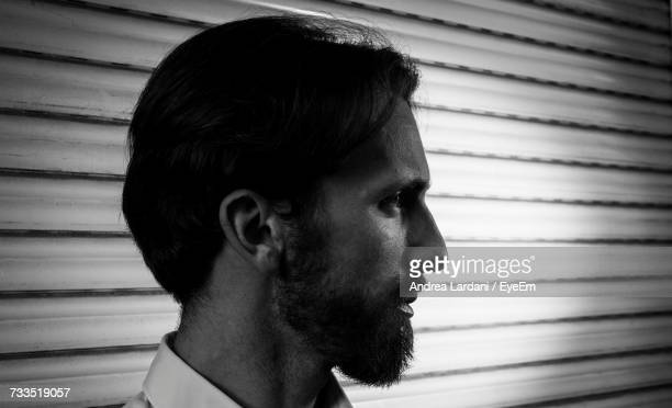 Close-Up Of Man Looking Away Against Wall