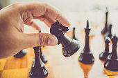 Closeup toned photo of man making move with black horse at chess game