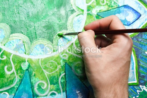 closeup of man painting green picture with circle pattern : Stock Photo