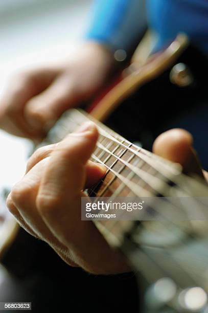 Close-up of man playing acoustic guitar
