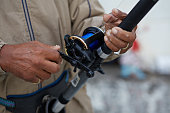 Close-up of man pulling line at fishing rod