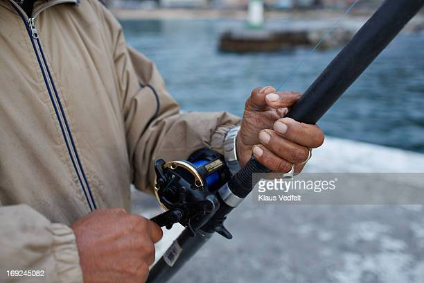 Close-up of man pulling the line on fishing rod