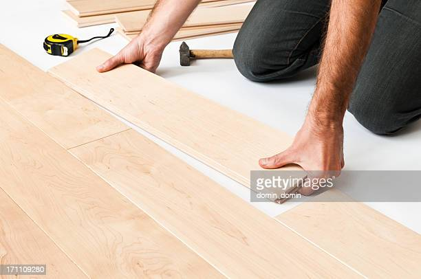 Close-up of man putting hardwood floor panels, floorboards