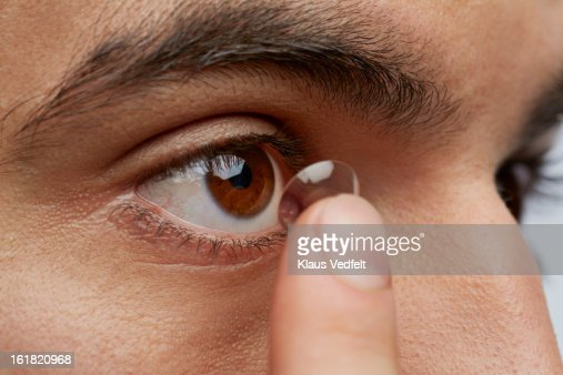 Close-up of man putting in contact lens : Stock Photo
