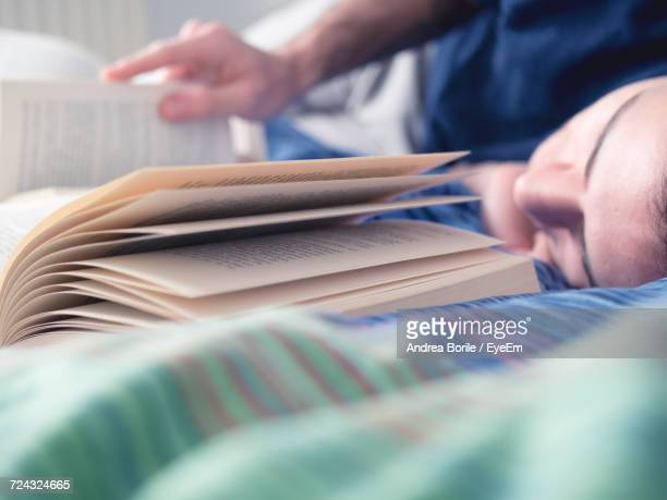 Close-Up Of Man Reading Book While Lying On Bed At Home
