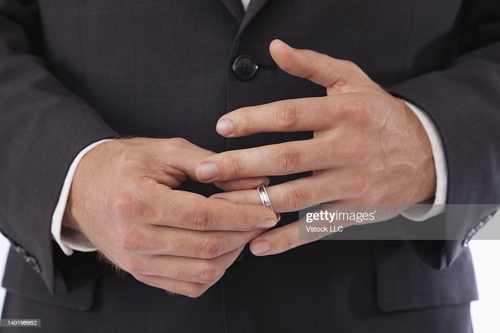 Close-up of man removing wedding ring from finger : Stock Photo