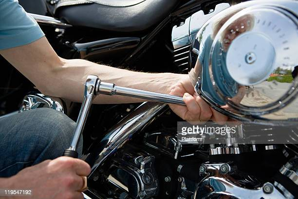 Close-up of man repairing vintage motorbike